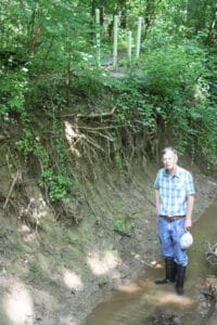 Scientist standing in an eroded streambed