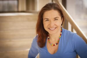 Headshot of Dr. Katharine Hayhoe with red hair, wearing a rainbow beaded necklace and a blue shirt.